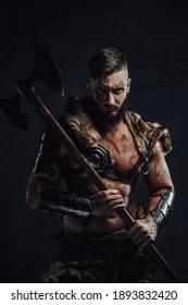 In dunkler Rüstung gekleidet mit fellschmutzigen und großartigen Viking-Kämpfer mit zwei Händen Axt auf seiner Schulter steht auf dunklem Hintergrund.