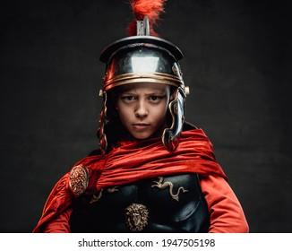 Dressed in legionary clothing cheerful boy in dark background