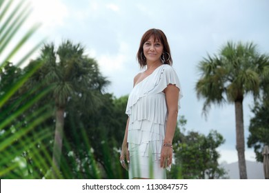 Dressed up young woman at outdoor by palm tree