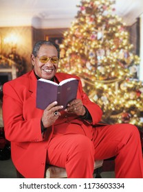 A dressed-up senior man happily reading his Bible in an elegant  Christmas-decorated living room.