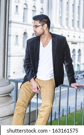Dressing in a black woolen blazer, white underwear and dark yellow pants, wearing glasses, a young professional with bread and mustache is causally sitting by a railing, relaxing and thinking.