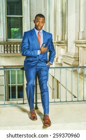 Dressing in blue suit, tie, leather shoes, putting a hand on chest, a young black businessman sitting on railing in vintage style office building, confidently looking at you. Instagram filtered look.