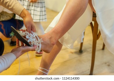 Dressing bride. Taking shoes, wedding dress, flowers, garter. Detail of dressing bride.