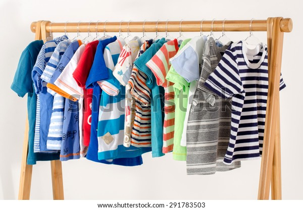 Dressing closet with clothes arranged on hangers.Colorful wardrobe of newborn,kids, toddlers, babies full of all clothes.Many t-shirts,pants, shirts,blouses, onesie hanging