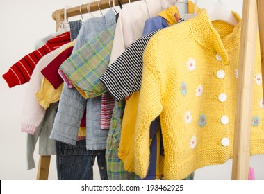 Dressing closet with complementary clothes arranged on hangers.Colorful wardrobe of newborn,kids, babies full of all clothes, shoes,accessories and toys