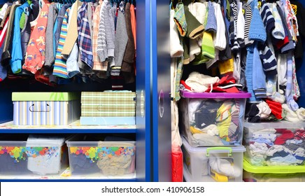 Dressing closet for kids with clothes arranged on hangers.Colorful wardrobe of newborn,kids, toddlers, babies full of all clothes.Many t-shirts,pants, shirts,blouses, onesie hanging