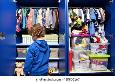 Dressing closet for kids with clothes arranged on hangers and teddy bears.Colorful wardrobe of newborn, toddlers, babies full of t-shirts,pants, shirts,blouses, onesie hanging, kid choosing clothes
