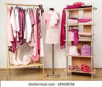 Dressing closet with pink clothes arranged on hangers and shelf, outfit on a mannequin. Wardrobe full of all shades of pink clothes, shoes and accessories.