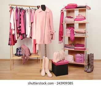 Dressing closet with pink clothes arranged on hangers and shelf, a coat on a mannequin. Fall winter wardrobe full of all shades of pink clothes, shoes and accessories.