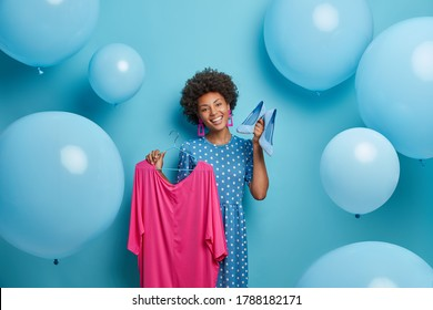 Dressing and clothing concept. Cheerful smiling fashionable woman demonstrates her new purchases, chooses outfit to wear, holds elegant pink dress on hanger and blue high heel shoes, stands indoor