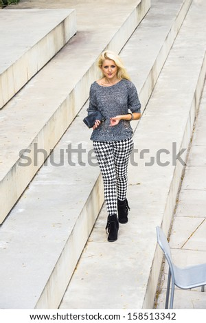 33efc8213fdc2 Dressing in a gray fashionable sweater, black and white pattern pants,  black boots, holding a black leather purse, a young blonde girl is walking  on steps.