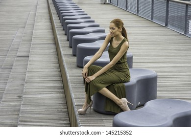 Dressing in a green Maxi Tank Dress and high heel shoes,  a young black girl is sitting on a modern style bench, smiling and relaxing. /Relaxing Outside