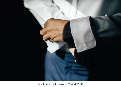 Dressing groom and preparing for ceremony on background