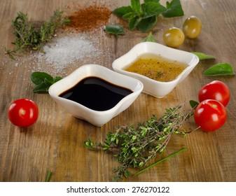 Dressing ingredients on a rustic background. Olive oil, balsamic vinegar, herbs, salt and pepper. Selective focus