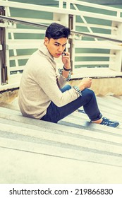 . Dressing in kitted sweater with shawl collar cardigan, jeans, rolling over cuff, a young guy is sitting on stairs by fence, talking on mobile phone, looking back.