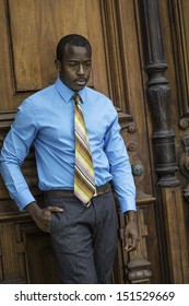 Dressing in a light blue shirt,  gray pants and a colorful tie, a young handsome black businessman is standing a old fashion style door, into deeply thinking. / Portrait of Young Black Businessman