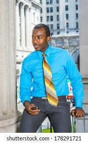 Dressing in a light blue shirt,  gray pants,  a pattern tie, a young black businessman is sitting outside a office building, holding a mobile phone, waiting for you. / Relaxing Outside