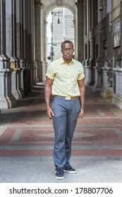 Dressing in a light blue shirt, a pattern tie, gray pants, wearing glasses, a black college student is standing on a walkway on campus, looking at you. / Portrait of College Student