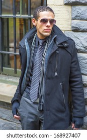 Dressing in a pea coat, tie and gloves, wearing sunglasses, a young guy is waiting outside by the window / Waiting outside