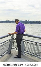 Dressing in a purple shirt, gray pants and leather shoes, a young guy with a little beard is facing a river, lowing down his head into deeply thinking. / Deeply Thinking