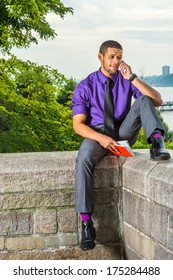 Dressing in a purple shirt, gray pants and a black tie, holding a red book, a college student with a little beard and mustache is sitting by a river on campus and talking on the phone. / Bad News