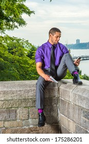 Dressing in a purple shirt, gray pants, a black tie, leather shoes, holding a book, a college student with a little beard, mustache is sitting by a river on campus, checking messages on smart phone.
