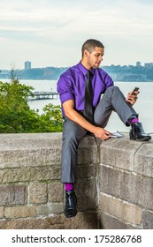 Dressing in a purple shirt, gray pants, a black tie, leather shoes, holding a book, a young handsome guy with a little beard, mustache is sitting by a river, checking messages on his smart phone./Text