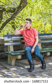 Dressing in a red Polo shirt, green pants and long leather boots, one hand touching his chin, a young handsome guy is sitting on a long chair  in the morning of a spring season, relaxing and thinking