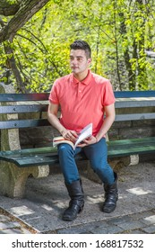 Dressing in a red Polo shirt, green pants and long leather boots, a young handsome guy is sitting on a long chair  in the morning of a spring season, reading a book. / Reading in the morning
