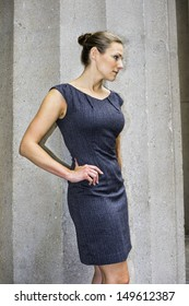 Dressing in a sleeveless work wear dress and with a tight top knot bun, a young pretty businesswoman is standing outside and taking a break. / Portrait of Businesswoman