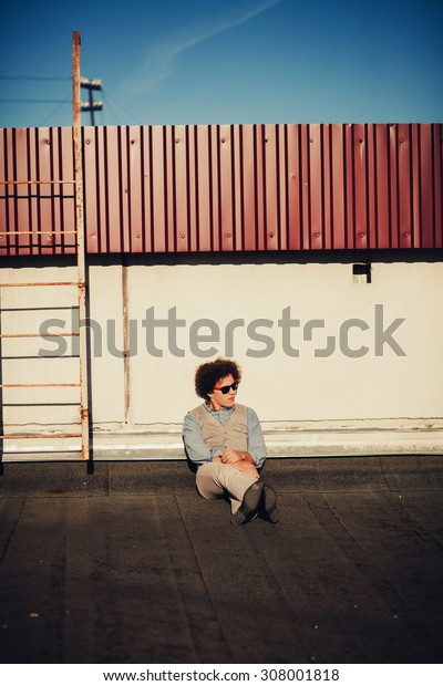 Dressing in a vest and shirt, leather boot shoes, a young handsome guy is sitting on roof