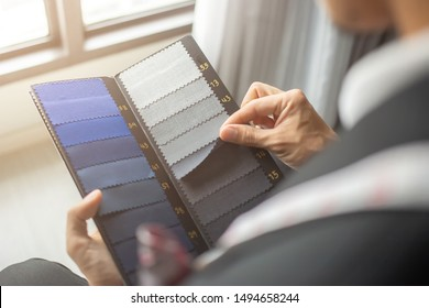The dressmaker is choosing the fabric to cut the suit. Customers are choosing the color of the fabric in order to tailor the suit.