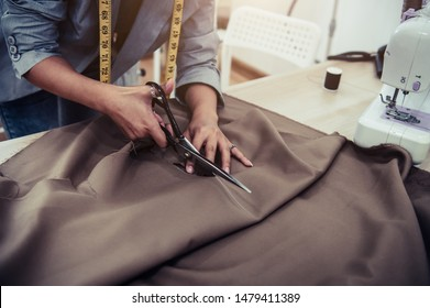 Dressmaker cutting dress fabric on sketch line with sewing machine. Fashion designer tailor or sewer in workshop studio designing new collection clothes. Business owner shop and entrepreneur concept