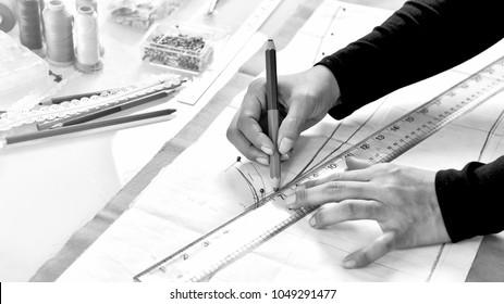 Dressmaker designer making pattern and measure garment, Asian fashion designer working in her showroom studio.