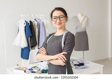 Dressmaker, fashion designer and tailor concept - Young dressmaker woman over clothes rack with dresses background