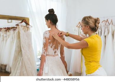 dressmaker helping the bride to put her wedding dress on in clothes shop.