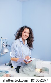 dressmaker looking at camera writing order of customers. sewing service