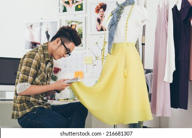 Dressmaker looking for skirt fabric color among the color samples