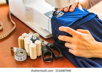 Dressmaker or seamstress works using sewing machine