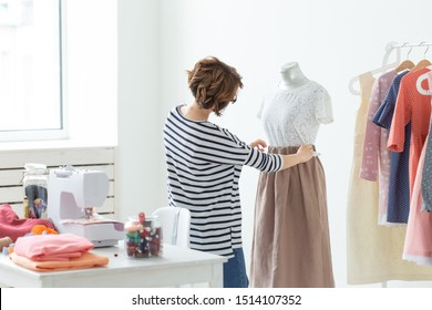 Dressmaker, Small-Sized Enterprises, fashion designer and tailor concept - Working process, designer decorates the outfit on the mannequin