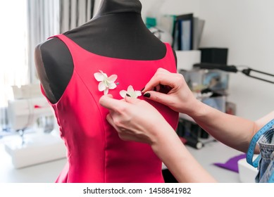 Dressmaker, tailor, fashion and showroom concept-portrait of a talented woman dressmaker working with textiles for tailoring. decorating the red dress