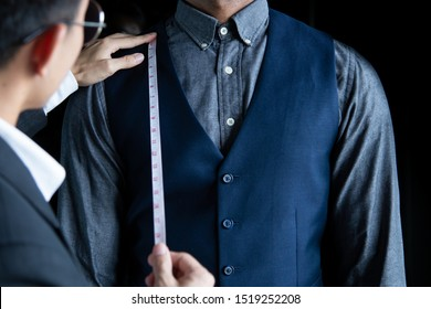 The dressmaker is using a tape measure to measure the length of the body on a black background.