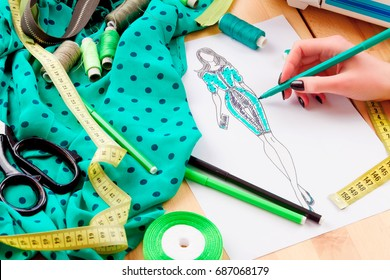 Dressmaker's workplace: scissors, ribbons, lace, pencils, sketch, fabric, measuring tape and band. Girl sketching a dress