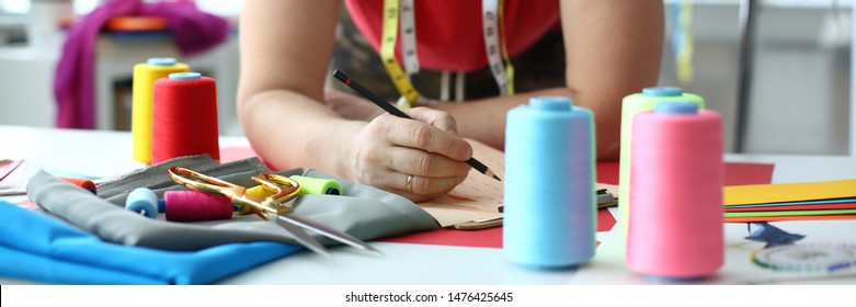 Dressmaking and Sewing Concept Fashion Designer. Male Dressmaker at Workplace. Craftsman with Measuring Tape on Neck. Fabric, Sewing Tools and Reels of Color Thread on Table. Handmade Clothes Bespoke