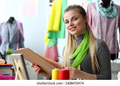 Dressmaking and Sewing Service Clothes Creation. Smiling Girl Needlewoman Holding Clipboard with Fashion Dress Draft. Cute Woman Sewer at Creative Working Space. Tailoring Entrepreneurship