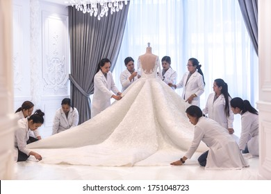 Dressmaking. Team of female workers making a big beautiful haute couture bridal wedding dress.