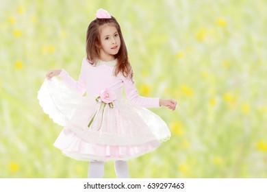 Dressy little girl long blonde hair, beautiful pink dress and a rose in her hair.She plays with her floors for her dress.Summer white green blurred background.