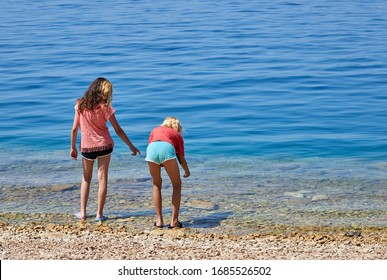 DREVENIK, CROATIA-July 3, 2019: Two friends collecting sea shells in Drevenik, Croatia.