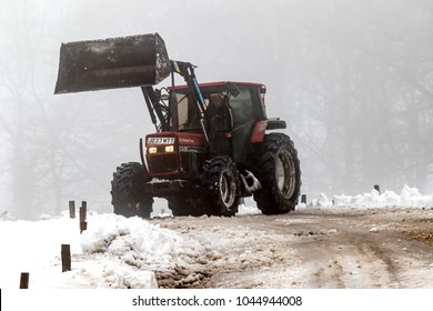Drewsteignton, United Kingdom, 3rd March 2018:- A tractor clears snow from a roadway after the Beast From The East Winter Storm
