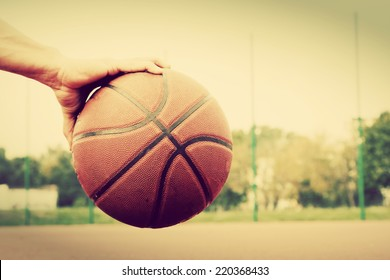 Dribbling the ball on basketball court. Streetball, training, sport. Real and authentic, vintage mood.